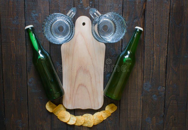 Den roliga ordningen av chiper, öl rånar, flaskor av öl och ett träbräde för mellanmål, på en träbrun tabell arkivfoto