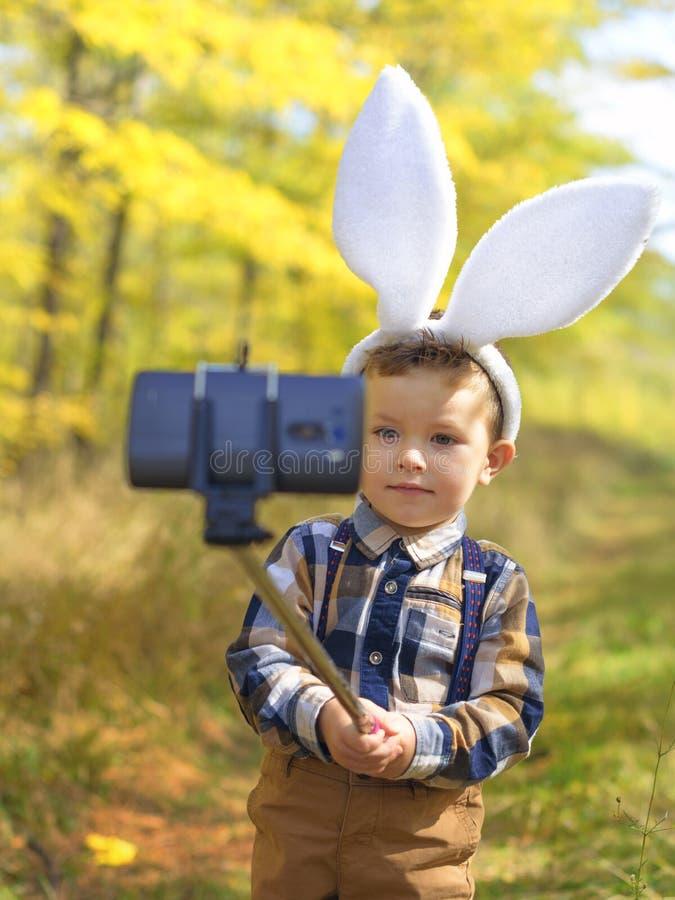 Den roliga pojken för den lilla ungen med påskkaninen gå i ax ta en selfie royaltyfri fotografi