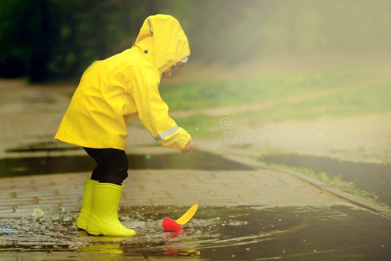Den roliga pojken ska spara dess plast- fartyg som sjönk i en pöl en pojke i en gul regnrock går i parkerar royaltyfri bild