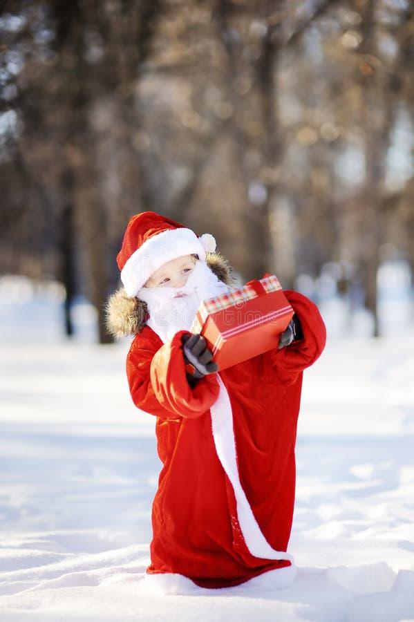 Den roliga pysen klädde som Santa Claus som rymmer den röda asken med julgåvan royaltyfri fotografi