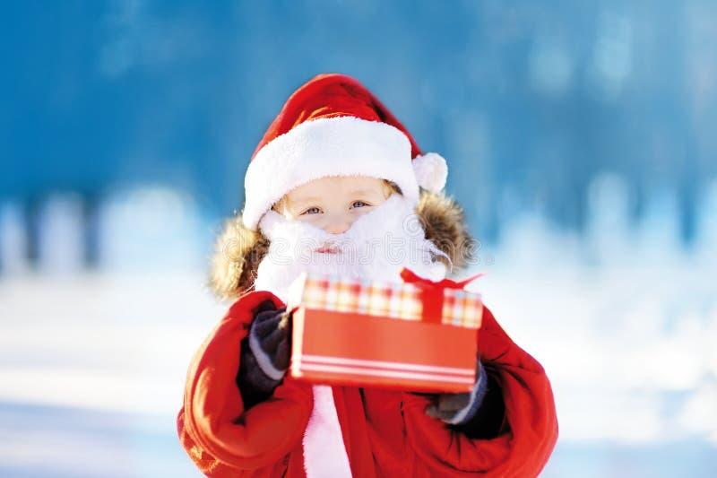 Den roliga pysen som bär den Santa Claus dräkten i den snöig vintern, parkerar arkivfoton