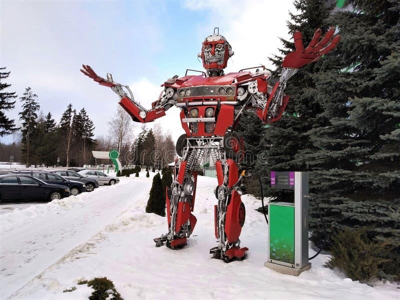 Den roliga roboten för humanoid metall den röda autoboaten, göras av bilreservdelar, tankar bensin, delar av kroppen av roboten, fotografering för bildbyråer