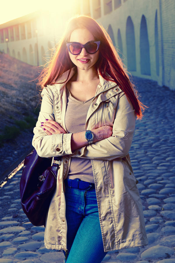 Den roliga stilfulla le härliga unga redhairkvinnan i hipster beklär anseende i gatan med den trendiga handväskan royaltyfri foto
