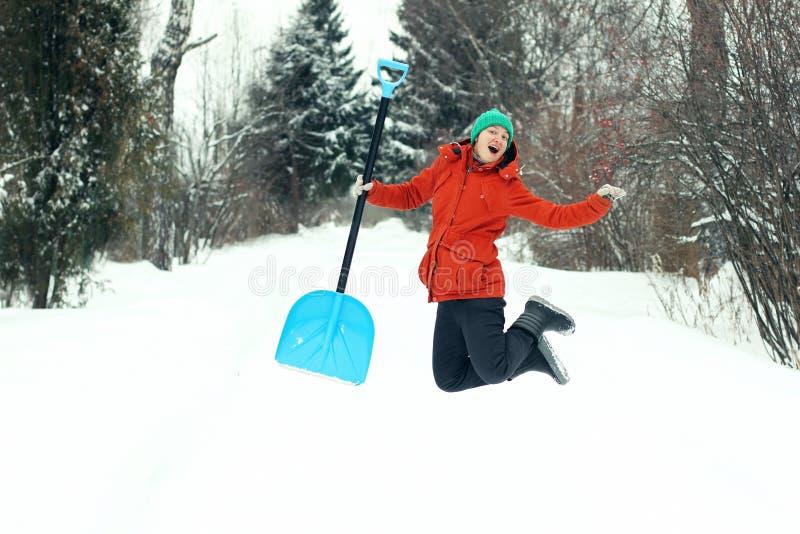 Den roliga unga kvinnan hoppar med snöskyffeln på den lantliga vägen Säsongsbetonat begrepp för vinter arkivbild