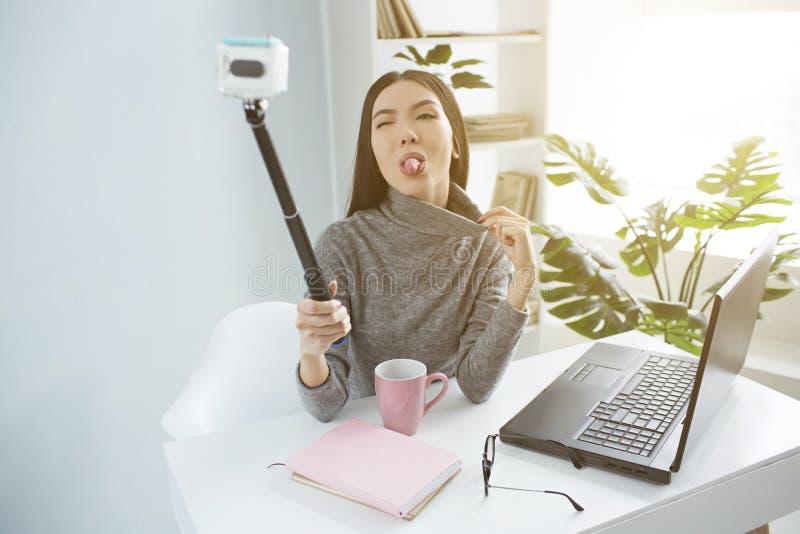 Den roliga unga kvinnan visar hennes tunga till kameran Hon är bloggeren och att anteckna hennes video hemma arkivfoto