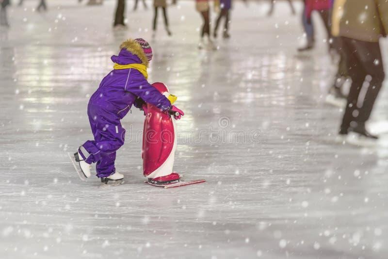Den roliga ungedet fria i parkerar på åka skridskor isbana för vinter, royaltyfria bilder