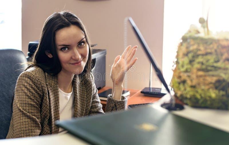 Den roliga visningen för flickakontorsarbetare tummar upp sammanträde på datoren på arbete royaltyfri bild