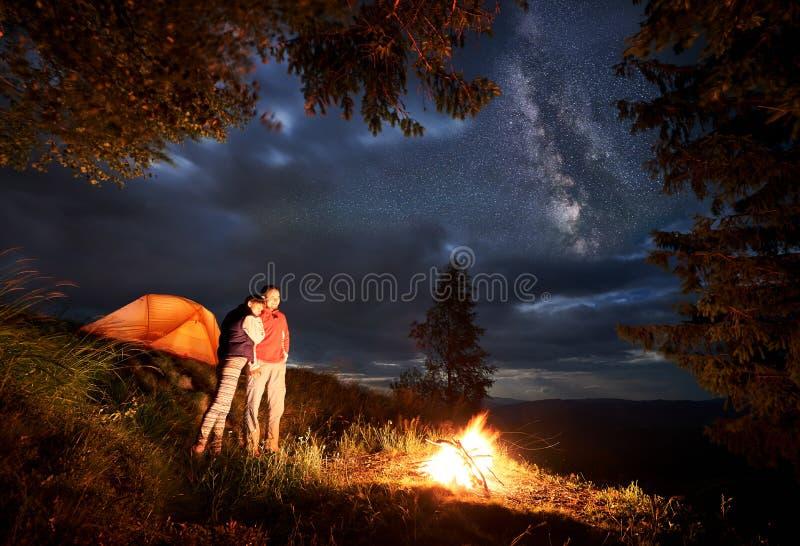 Den romantiska aftonen av barn kopplar ihop i berg vid brand under den stjärnklara himlen royaltyfria bilder