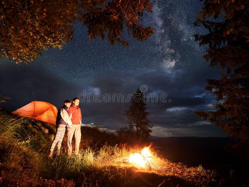 Den romantiska aftonen av barn kopplar ihop i berg vid brand under den stjärnklara himlen royaltyfri fotografi
