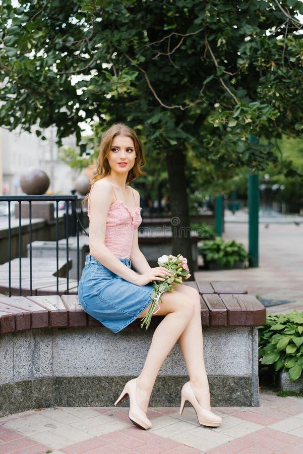 Den romantiska bilden av en ung flicka som går på en sommargata i, parkerar med en bukett av rosor, stadsrekreation och går Sitta arkivfoto