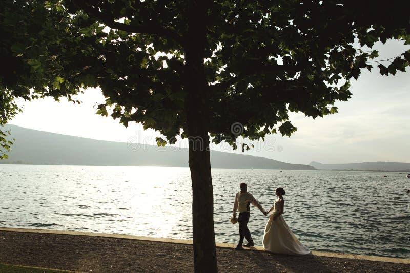 Den romantiska den nygift personparbruden och brudgummen på solnedgången sätter på land nära se royaltyfri fotografi