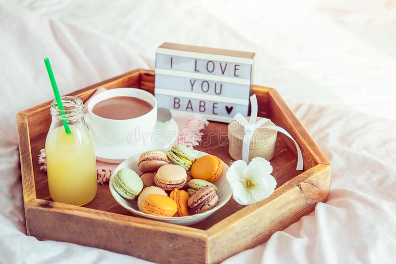 Den romantiska frukosten i säng med älskar jag dig behandla som ett barn text på den tända asken Kopp kaffe-, fruktsaft-, makron- arkivbild