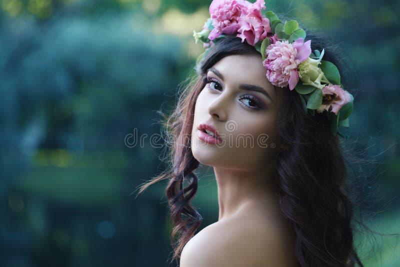 Den romantiska kvinnan med pionen blommar utomhus royaltyfri fotografi