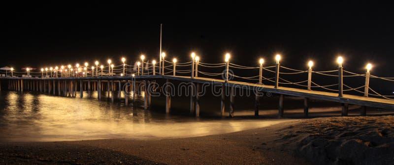 Den romantiska sommarnatten och sand sätter på land med den upplysta pir arkivfoto