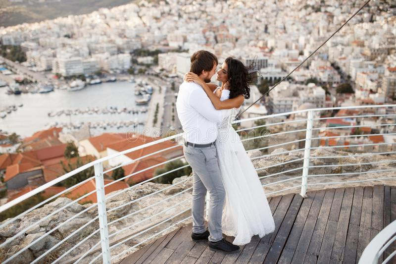 Den romantiska st?enden av tv? h?rliga unga par, poserar, i att gifta sig kl?der, bak stad i Grekland, under sommarsolnedg?ng arkivfoto