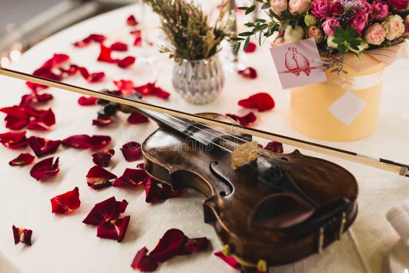 Den romantiska tabellinställningen med härliga blommor i ask, steg kronblad och fiolen royaltyfri fotografi