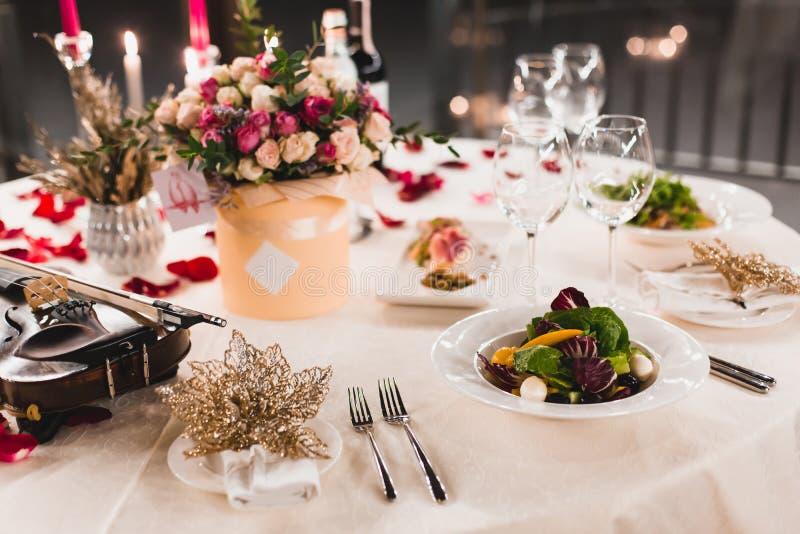 Den romantiska tabellinställningen med vin, härliga blommor i ask, tomma exponeringsglas, steg kronblad och stearinljus fotografering för bildbyråer