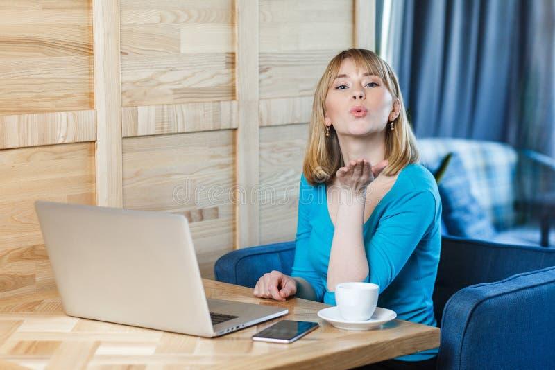 Den romantiska ung flickafreelanceren med blont guppar frisyrhår i blå blus sitter bara i kafé och arbetar på bärbara datorn och arkivbilder
