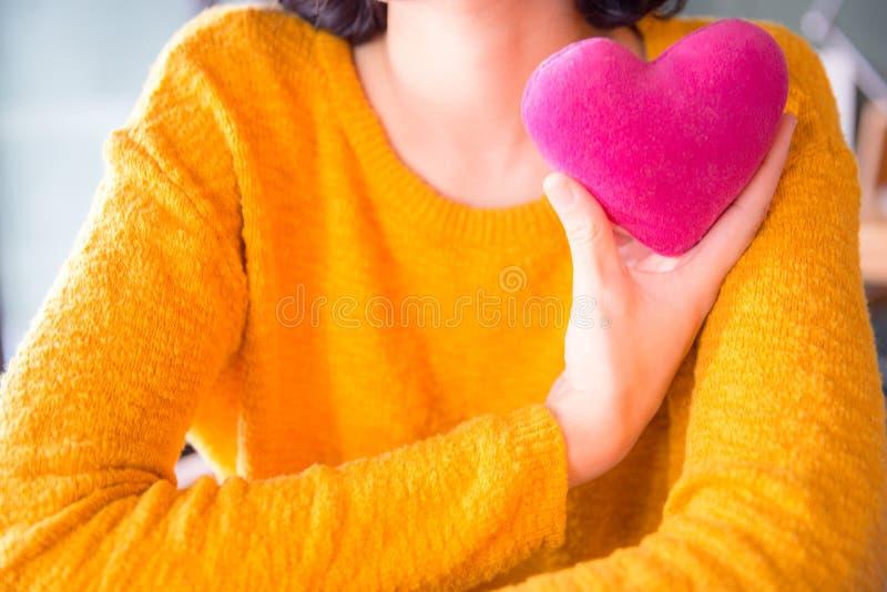 Den romantiska unga asiatiska kvinnan med hjärta-formade rosa färger kudde arkivfoto