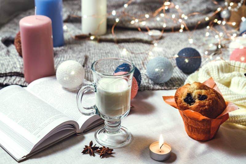 Den romantiska vintern och nytt års mjölkar den inre sikten för stil med en stearinljus, en bok, en girland, en kaka och ett expo arkivfoton