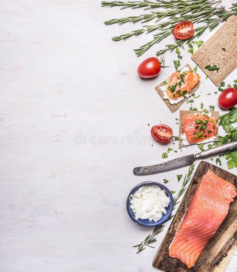 Den rosa laxfilén med tomater, rosmarin, ostmassaost, tappningbestick, bröd för smörgåsar gränsar, förlägger för text på trär royaltyfria foton