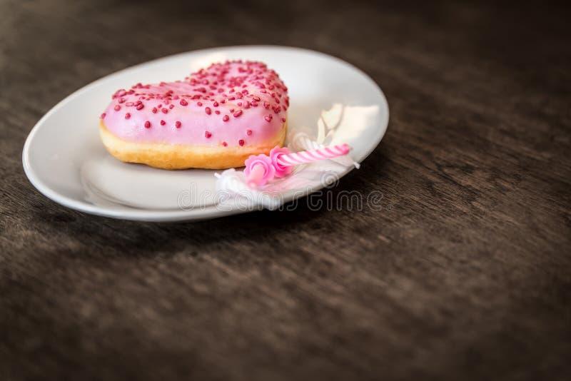 Den rosa munken med isläggning ligger på en vit platta royaltyfria foton