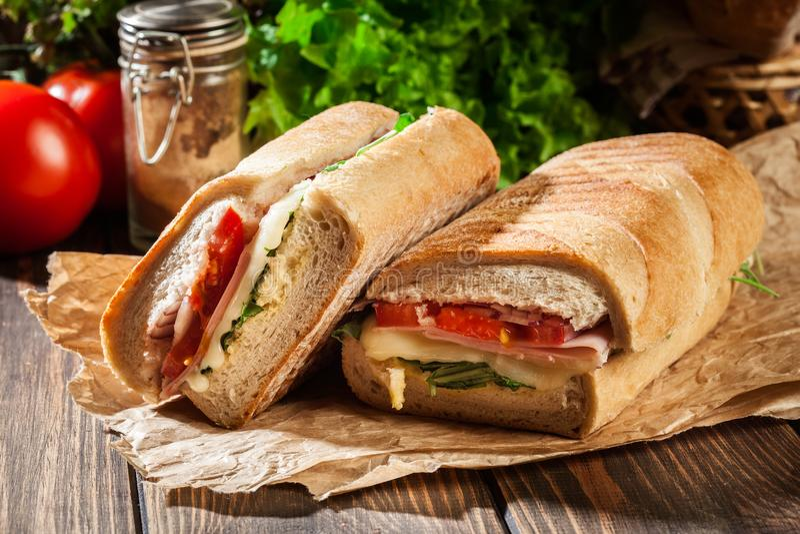 Den rostade paninien med skinka, ost och arugula skjuter in arkivbilder