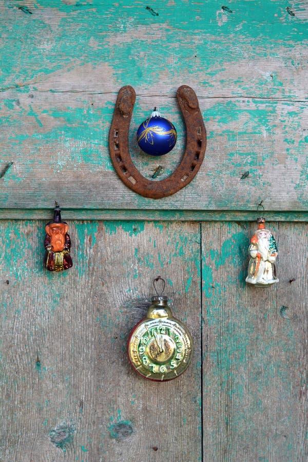 Den rostiga hästskon, julsnögubbeleksaker och tappning tar tid på på dörr royaltyfria foton