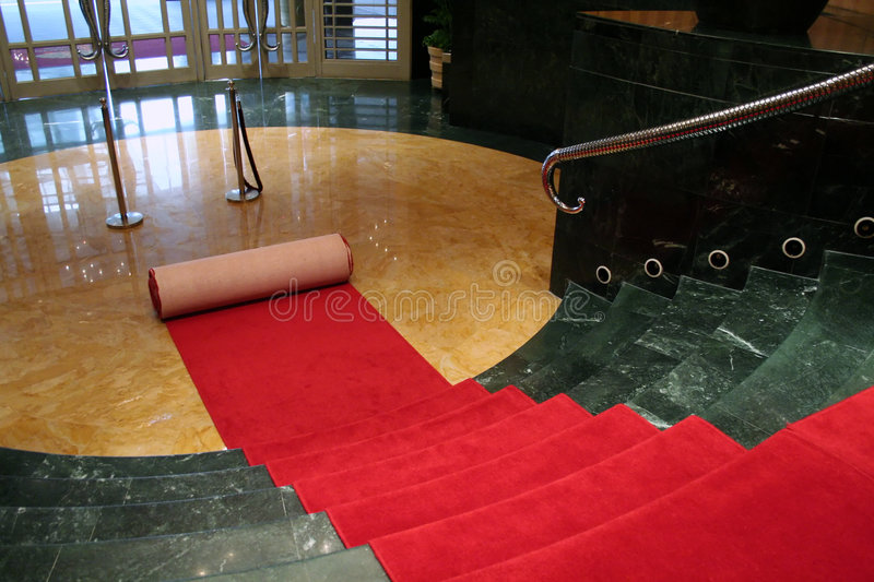 Den roten Teppich heraus rollen stockbild