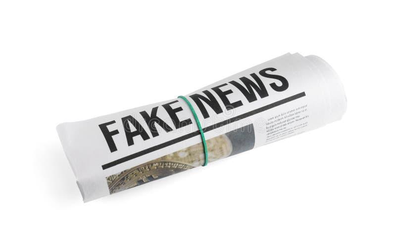 Den rullande tidningen med rubriken FEJKAR NYHETERNA på vit bakgrund arkivfoton
