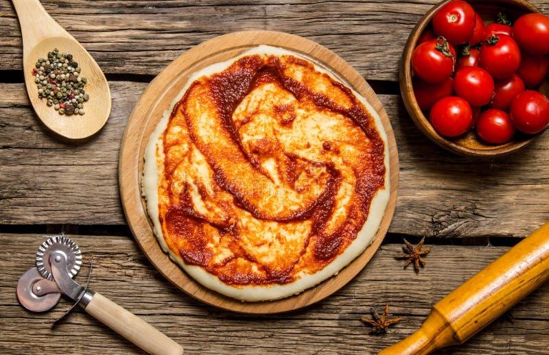 Den rullande ut pizzadegen med den tomatsås, kavlen och kryddor royaltyfri fotografi