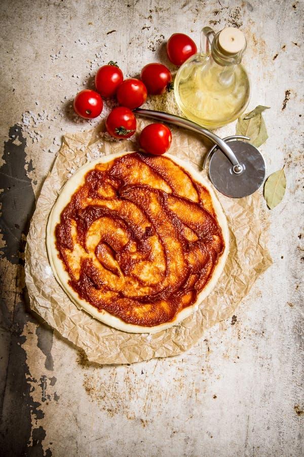 Den rullande ut pizzadegen med tomater, tomatdeg och olivolja royaltyfri bild