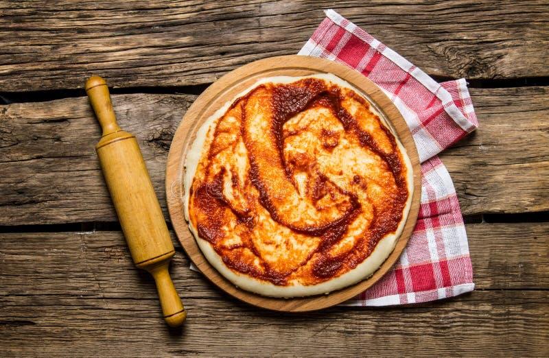 Den rullande ut pizzadegen med tomatsås och med en kavel på tyget royaltyfria foton
