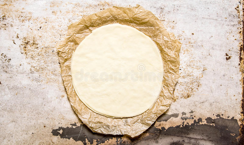 Den rullande ut pizzadegen på det gamla papperet arkivfoton
