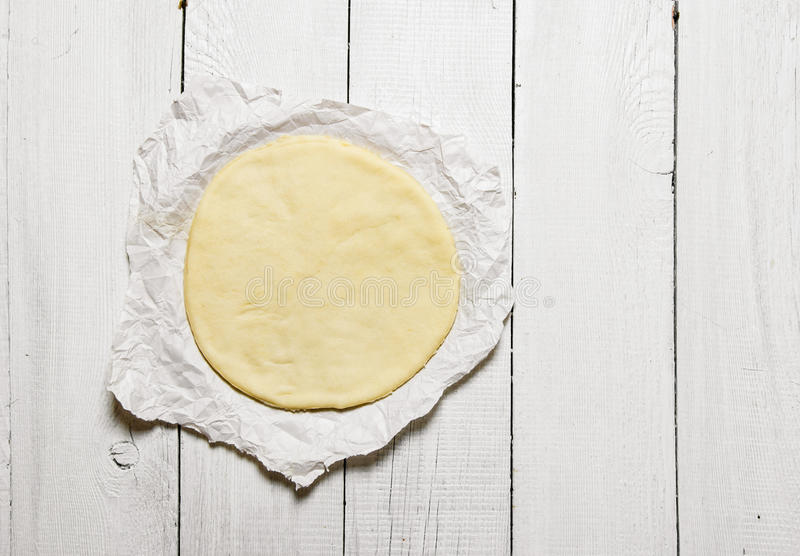 Den rullande ut pizzadegen på papperet arkivbild