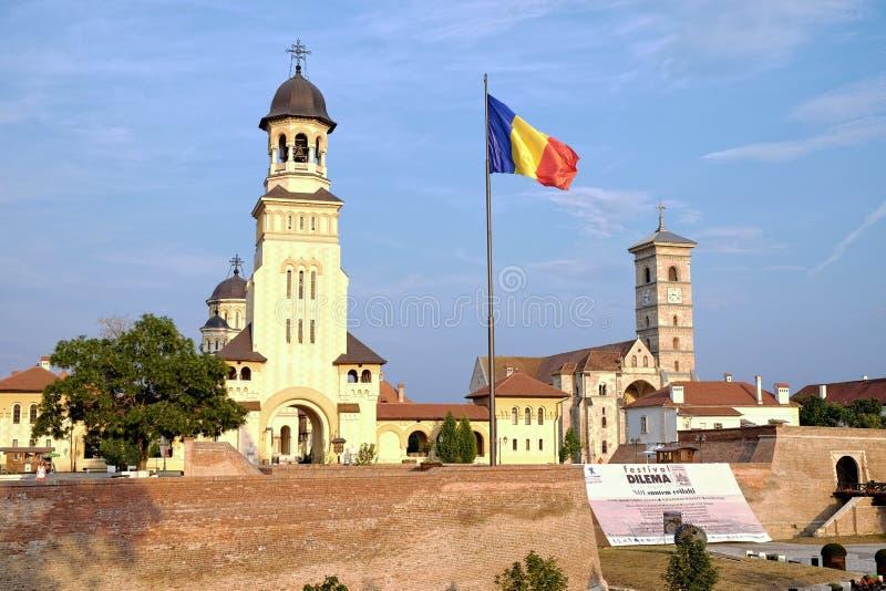 Den rumänska flaggan som vinkar mellan den ortodoxa kröningdomkyrkan och Sten Michael Roman Catholic Cathedral i den Carolina Cit royaltyfria foton