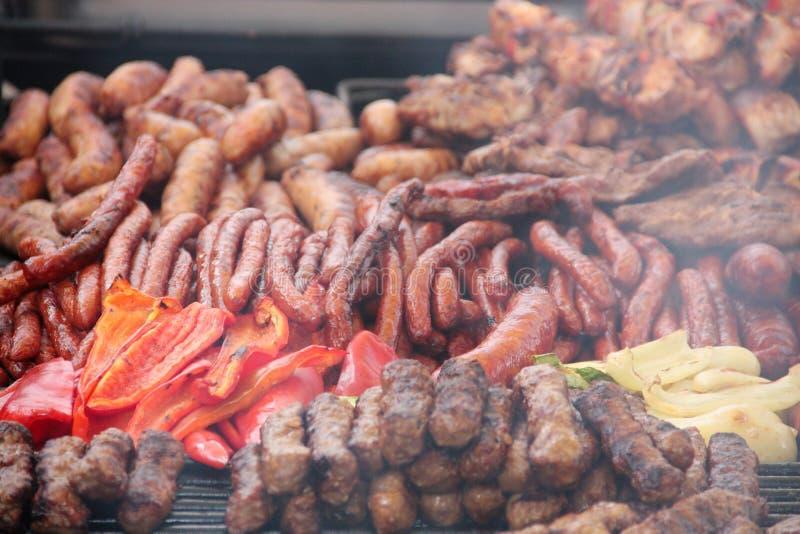 Den rumänska mixeda grillen med för griskött, fega och traditionella tunna korvar för nötkött som, säljs på en gatamat, stannar royaltyfria bilder