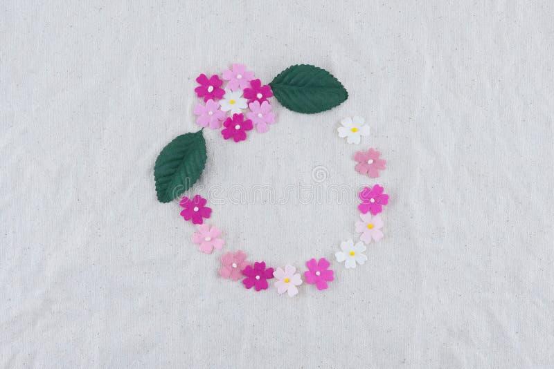 Den runda kransen som göras från rosa färger, tonar pappers- blommor arkivfoton