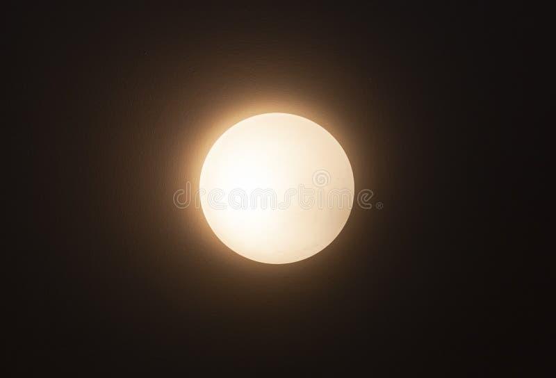 Den runda lampettlampan glöder över den mörka väggen arkivfoton