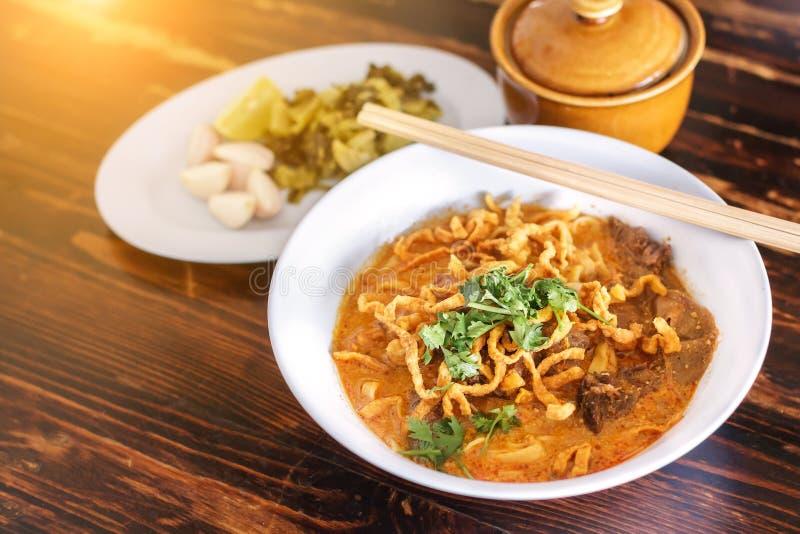 Den ryktade Khao för nudelsoppa soien med nötkött och den kryddiga kokosnöten mjölkar på den wood tabellen royaltyfri foto