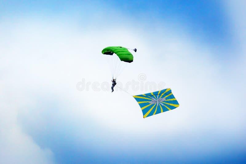 Den ryska fallskärmsjägaren hoppar med hoppa fallskärm med flaggan av ryskt flygvapen på klar blå himmel och vit molnbakgrund arkivfoto