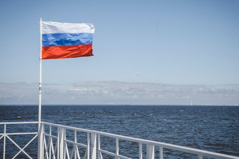Den ryska flaggan flyger mot havet royaltyfria bilder