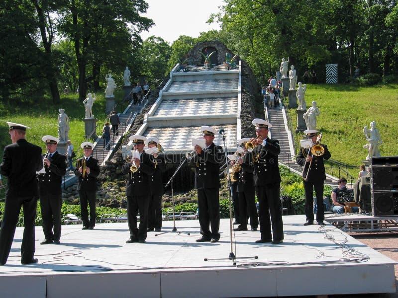 Den ryska sjö- orkesteren utför för turister på den formella trädgården nära berget för springbrunnkaskadschack royaltyfri foto