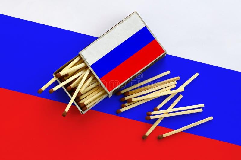 Den Ryssland flaggan visas på en öppen tändsticksask, som flera matcher faller från och lögner på en stor flagga royaltyfria bilder