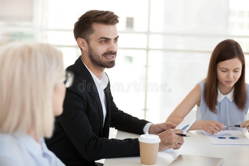Den säkra affärsmannen sitter på tabellen, diskuterar projekt på företagsmötet royaltyfri fotografi