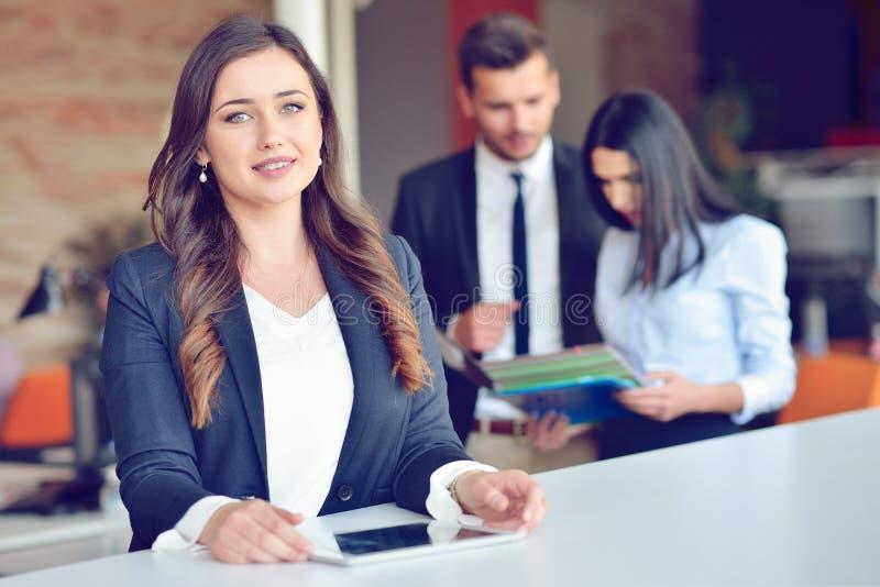 Den säkra attraktiva unga affärskvinnan med minnestavlan i händer i modernt kontor startar upp kontoret royaltyfri fotografi