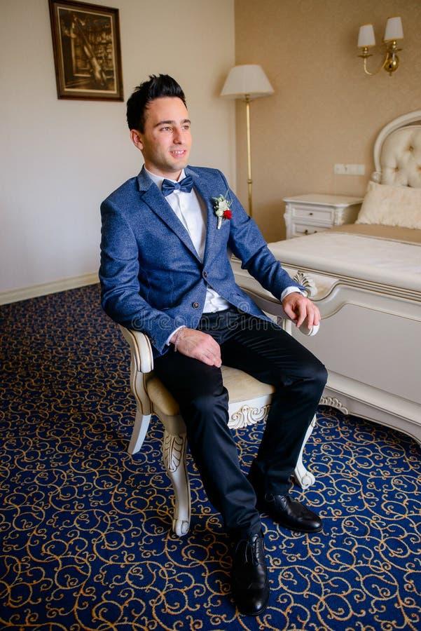 Den säkra brudgummen i blåttdräkt sitter på stolen royaltyfri foto