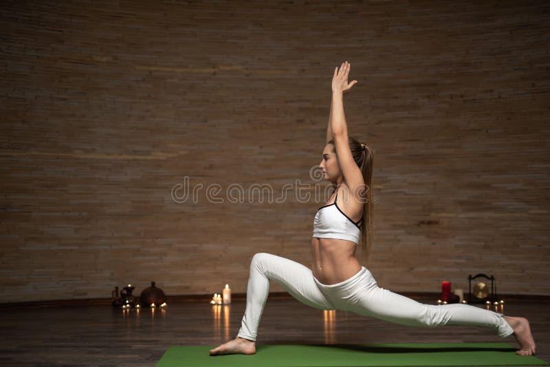 Den säkra damen som öva krigaren, poserar, medan stå på den matta yogan fotografering för bildbyråer