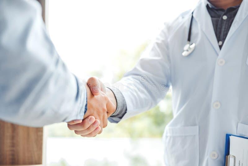 Den säkra doktorn som skakar händer med patienter, talar i hospitaen fotografering för bildbyråer