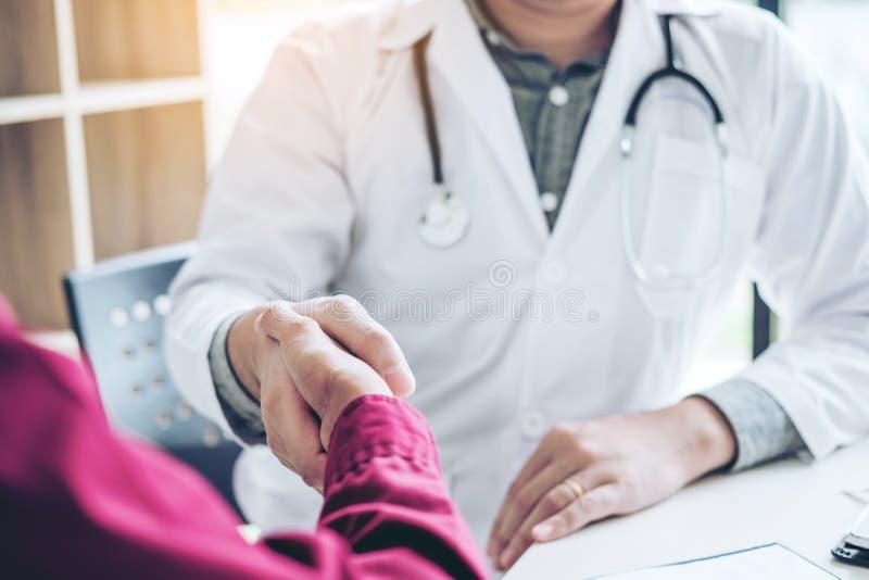 Den säkra doktorn som skakar händer med patienter, talar i hospiten royaltyfria bilder